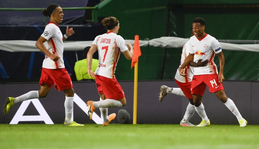 Leipzig's Tyler Adams, right, celebrates with teammates after scoring his team's second goal during the Champions League quarterfinal match between RB Leipzig and Atletico Madrid at the Jose Alvalade stadium in Lisbon, Portugal, Thursday, Aug. 13, 2020. (Lluis Gene/Pool Photo via AP)