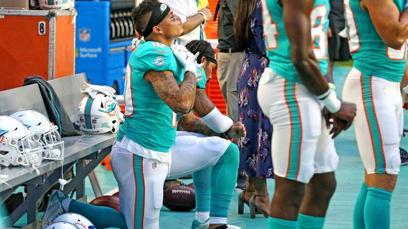 Miami Dolphins receivers Kenny Stills and Albert Wilson kneel during the national anthem as they prepare to play the Tampa Bay Buccaneers at Hard Rock Stadium in Miami Gardens, Fla., on Thursday.