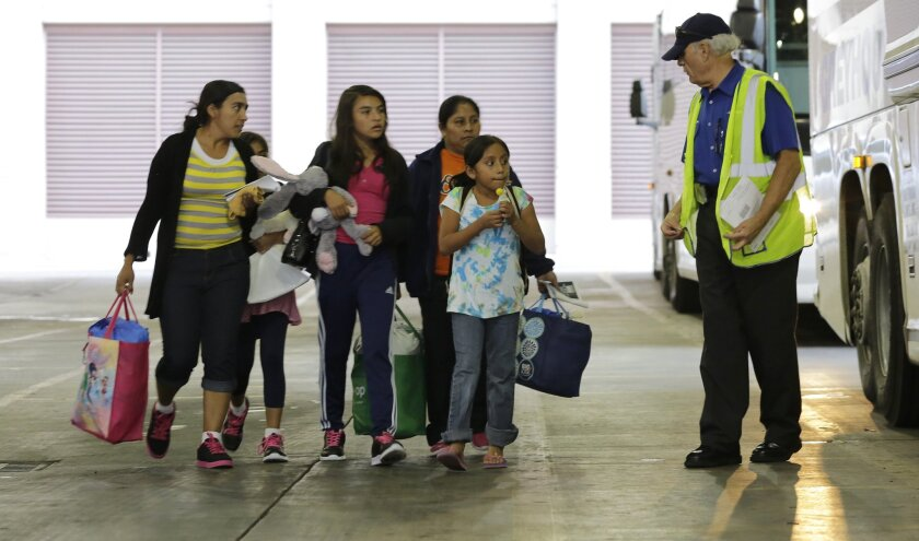 Immigrants from El Salvador and Guatemala who entered the country illegally prepare to board a bus last month in San Antonio after they were released from a family detention center in Texas.