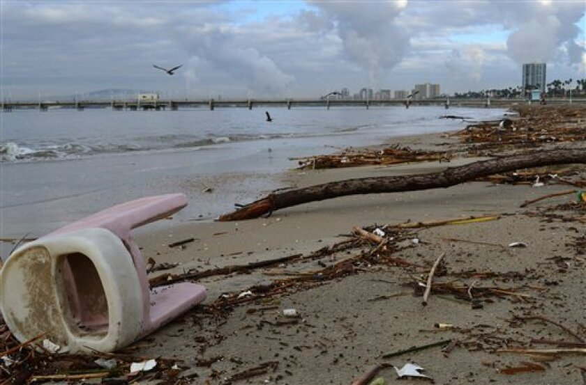 A baby's high chair lays along a debris covered beach in Long Beach, Calif. on Thursday, Dec. 23, 2010. The rain washed trash, pesticides and bacteria into waterways and prompted health warnings. Four beaches were closed in Northern California's San Mateo County, and another 12 miles of beach from