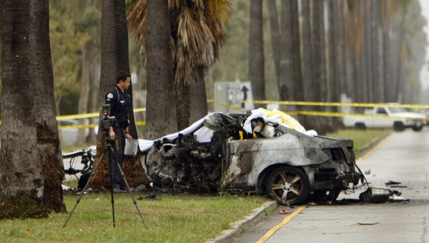 An LAPD officer investigates the scene of a single vehicle accident, where a driver was killed when his vehicle crashed into a tree and caught fire in the Hancock Park area of Los Angeles.