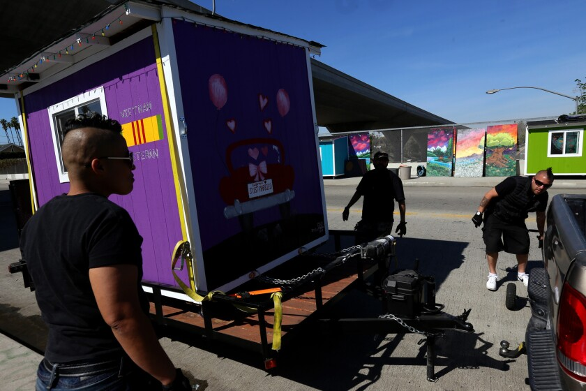 Elvis Summers, right, with the help of Marisol Viera, left, and Angel Bonillatercero, removes one of 37 small homes he built for the homeless in Los Angeles on February 24.