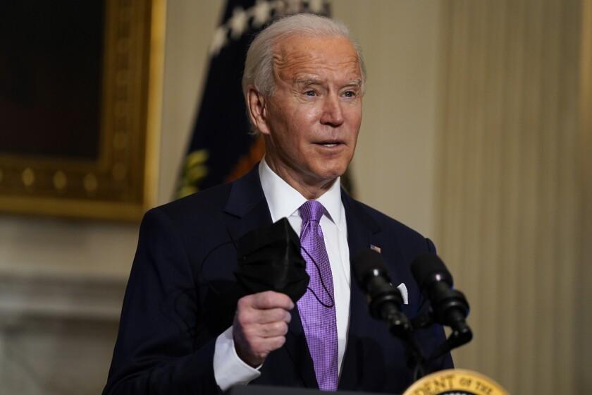 El presidente Joe Biden sostiene su mascarilla