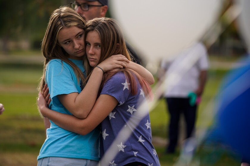 SANTA CLARITA, CALIF. - NOVEMBER 15: Sisters Isabella Esser, 16, and Sophoia Esser, 12, hug, as a memorial grows as people place flowers and pay their respects at Central park on Friday, Nov. 15, 2019 in Santa Clarita, Calif. The school remains closed a day after a shooting where a teenage boy gunned down fellow students on November 14, 2019. (Kent Nishimura / Los Angeles Times)