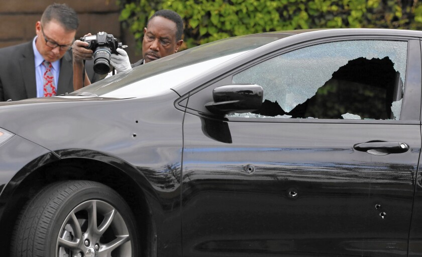 Investigators examine a car where a man was shot to death and two others were wounded.