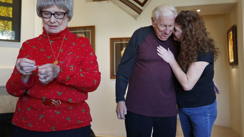 Joice Curry hugs her dad Andy Truban while Dora Truban works on a Christmas ornament..