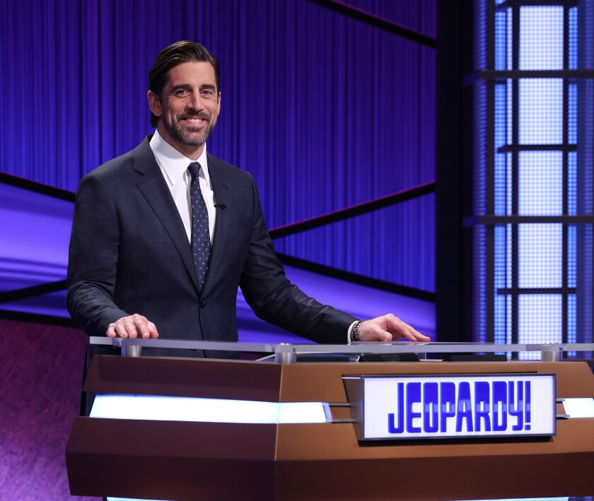 "Aaron Rodgers stands at a lectern that says ""Jeopardy!"""