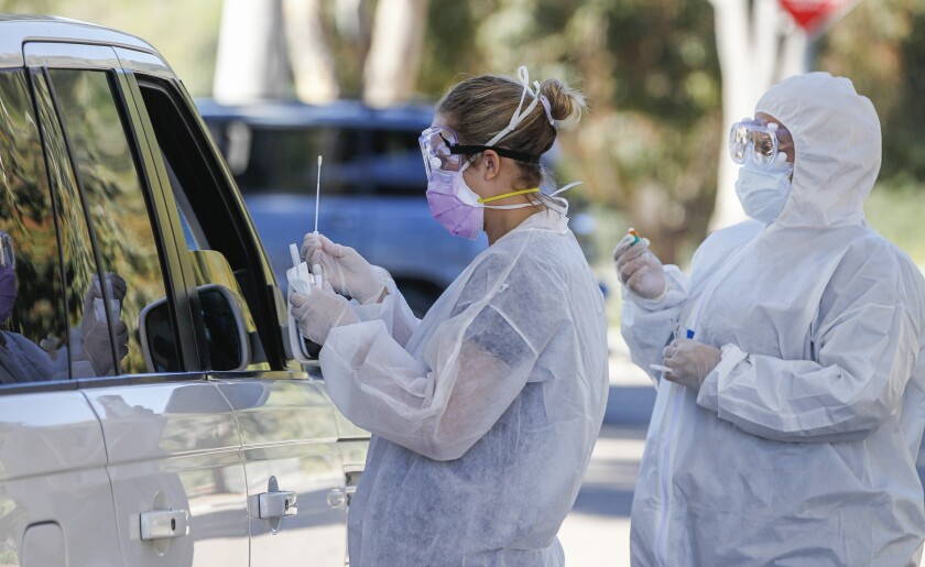 At a drive up testing site, Covid Clinic medical assistants Rhiannon Weik (left) and Arely Gutierrez (right) collect samples for Coronavirus COVID-19 testing at the San Elijo campus of Mira Costa College on April 15, 2020 in Cardiff, California.