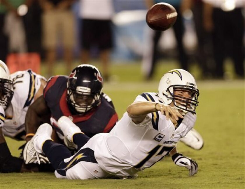San Diego Chargers quarterback Philip Rivers, right, throws under pressure from Houston Texans outside linebacker Whitney Mercilus during the first half of an NFL football game Monday, Sept. 9, 2013, in San Diego. (AP Photo/Gregory Bull)