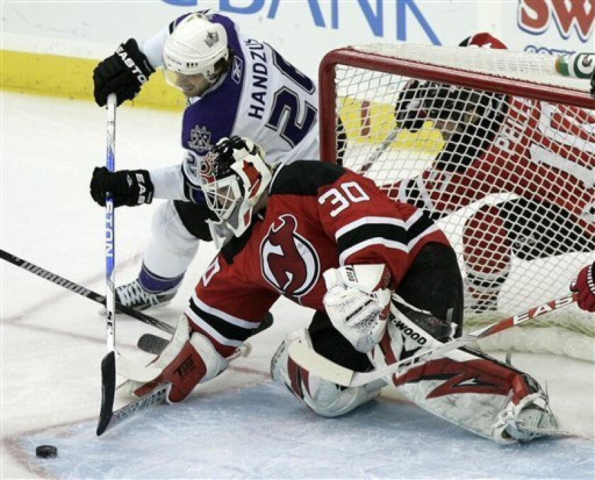 New Jersey Devils goalie Martin Brodeur (30), blocks the stick of Los Angeles Kings' Michal Handzus (26), of Slovakia, as he makes a save during the second period in an NHL hockey game at Prudential Center in Newark, N.J., Sunday, Jan. 31, 2010. (AP Photo/Rich Schultz)
