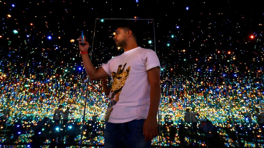 """Scott Reyes, 26, of Los Angeles, stands inside Yayoi Kusama's """"Infinity Mirrored Room -- The Souls of Millions of Light Years Away"""" at the Broad."""