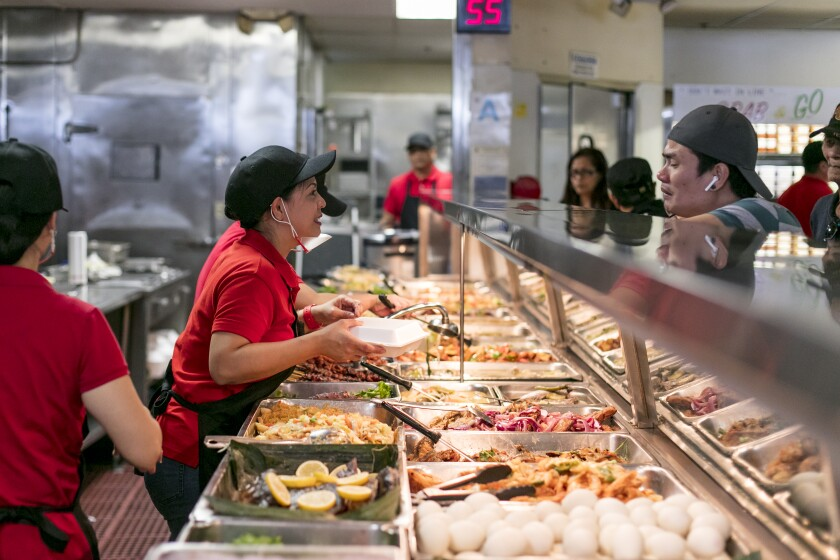 A member of the staff helps a customer at the turo turo hot-food counter at Arko Foods International.