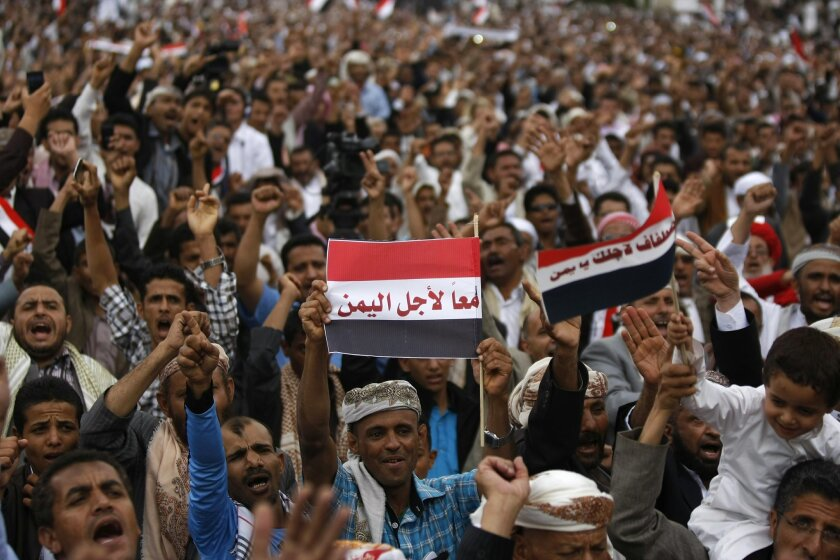 """A Yemeni government supporter holds a representation of the national flag with Arabic writing that reads, """"Together for Yemen,"""" during a rally against Hawthi Shiite rebels in Sanaa, Yemen, Friday, Sept. 5, 2014. The conflict between Hawthis and the government is rooted in enmity between the Shiite rebels and rival Sunni militias that are linked to the Muslim Brotherhood group and its political arm, the Islah party, which is part of the government. (AP Photo/Hani Mohammed)"""