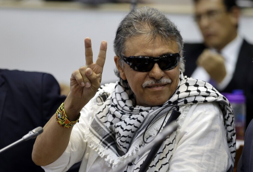 FILE - In this June 12, 2019 file photo, former FARC rebel Seuxis Hernandez, also known as Jesus Santrich, flashes a victory sign at journalists as he attends a session of the Chamber of Representatives at the Colombian congress in Bogota, Colombia. The rebel leader who abandoned a 2016 peace deal with Colombia's government and had been at large for three years was killed in Venezuela on Monday, May 18, 2021, according to a statement published by his new armed movement. (AP Photo/Fernando Vergara, File)