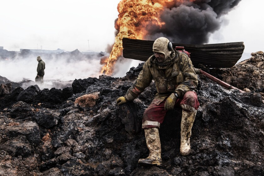 An Iraqi firefighter takes a break amid charred landscape as flames and smoke billow from an oil well set afire by retreating Islamic State fighters.