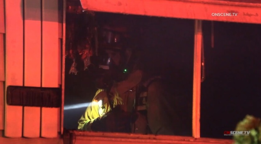 A firefighter walks through a burned mobile home Friday night in Lakeside.