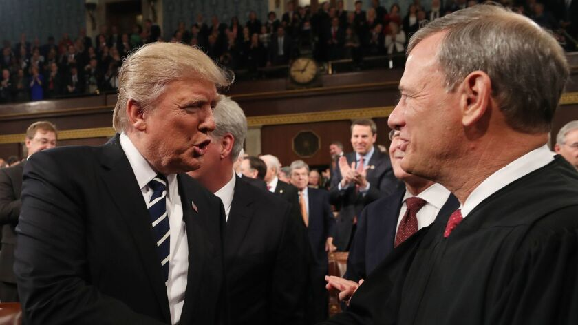 President Trump shakes hands with US Supreme Court Chief Justice John G. Roberts Jr.