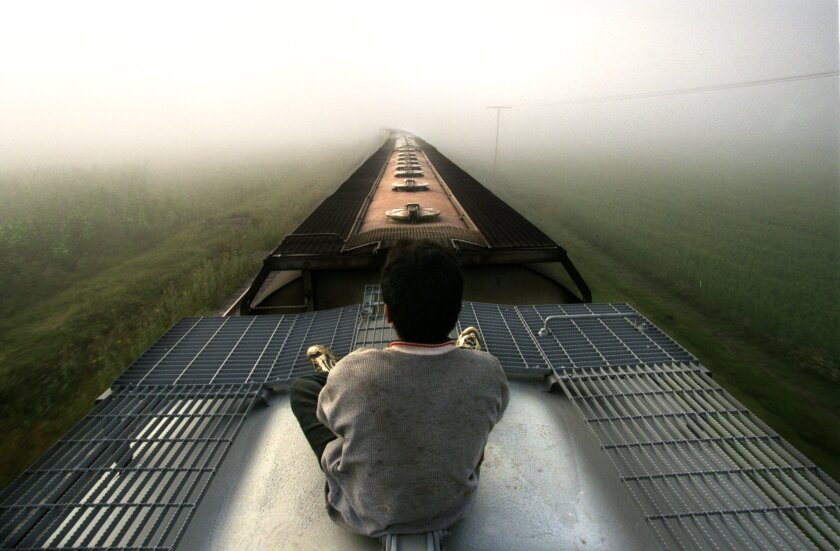 A lone Central American youth rides atop a freight train as it heads into a fog bank near Teotihuacan, Mexico.