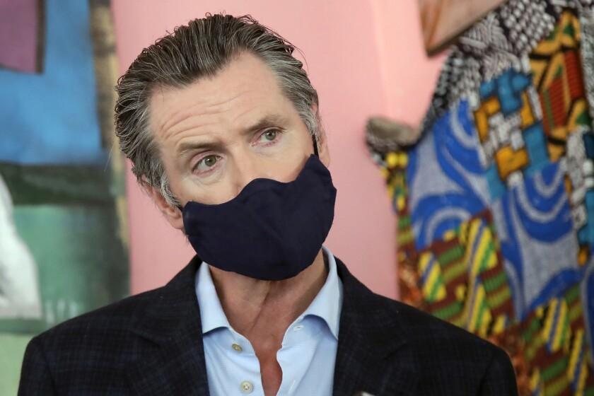 Gov. Gavin Newsom wears a mask as he speaks to reporters in June.