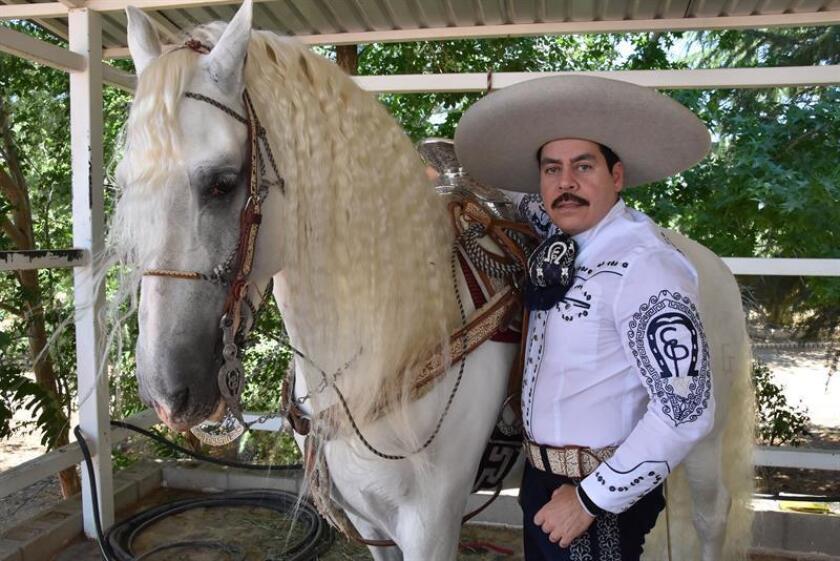 Fotografía fechada el 13 de junio de 2018 que muestra al intérprete de música regional mexicana Ezequiel Peña mientras posa junto a uno de sus caballos durante una entrevista con Efe en su rancho en Hesperia, California (EE.UU.). EFE