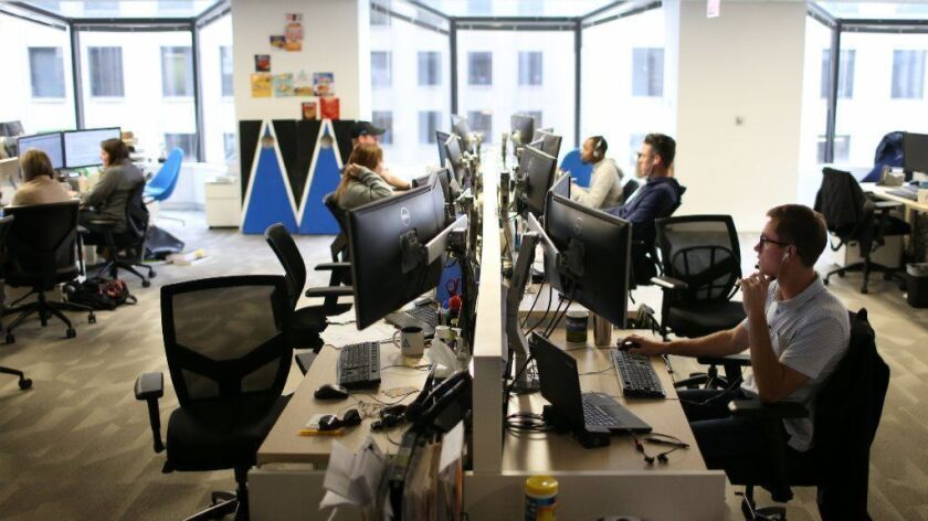 Matt Reasons, right, a finance analyst at Avant, works with others at the online lender's Loop office on Sept. 24, 2018. The 6-year-old company is one of a handful of Chicago unicorns — startups that are worth $1 billion or more.
