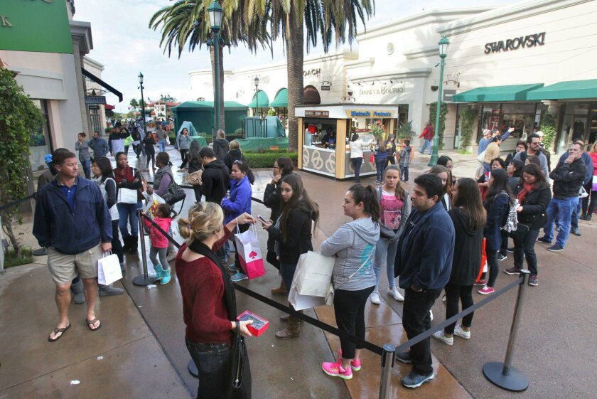 Shoppers line up outside the Kate Spade store at the Carlsbad Premium Outlets on Friday to take advantage of a 60 percent discount on everything in the store.