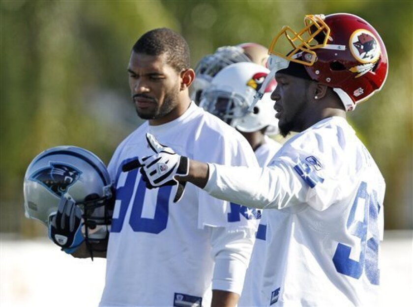 Carolina Panthers' Julius Peppers (90) talks to Washington Redskins' Brian Orakpo (98) during NFC NFL football practice at the Pro Bowl on Thursday, Jan. 28, 2010, in Fort Lauderdale, Fla. (AP Photo/J Pat Carter)