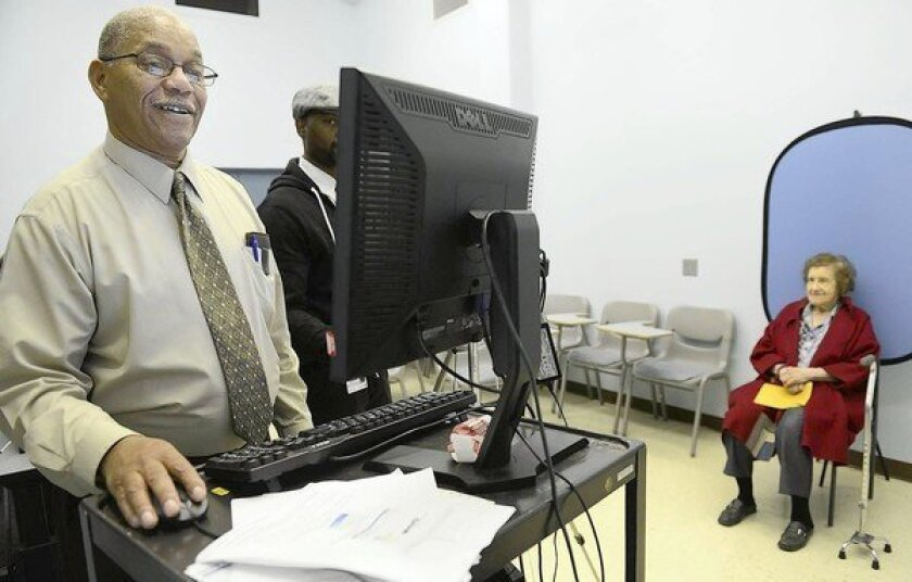Joseph Strickland prepares a voter identification card for Sophie Masloff, 94, in Pittsburgh. A judge blocked Pennsylvania's voter ID law from taking effect in the November election.