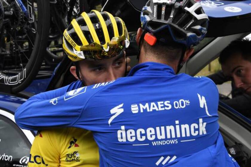 France's Julian Alaphilippe is comforted by a teammate after losing his yellow jersey Friday during the storm-shortened Stage 19 of the Tour de France.