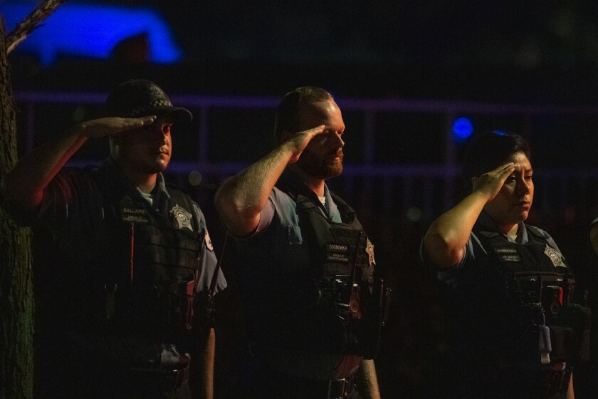Chicago police officers salute as a procession for a police officer who was shot and killed earlier during a traffic stop at 63rd and Bell drives by the Cook County Medical Examiners Office, Sunday, Aug. 8, 2021. (Tyler LaRiviere/Chicago Sun-Times via AP)