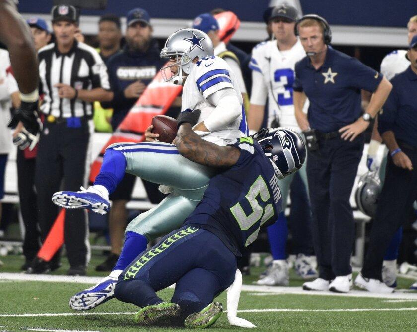 Dallas Cowboys' Matt Cassel (16) is sacked by Seattle Seahawks' Bruce Irvin (51) as Cowboys head coach Jason Garrett, rear, watches in the second half of an NFL football game Sunday, Nov. 1, 2015, in Arlington, Texas. The Seahawks won 13-12. (AP Photo/Michael Ainsworth)