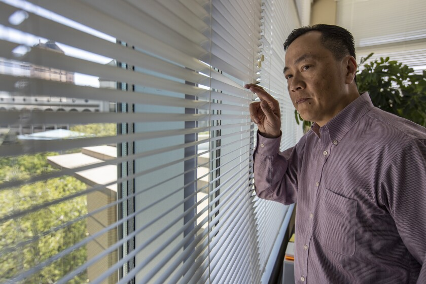 Sacramento City Manager Howard Chan looks through the window blinds at his office.