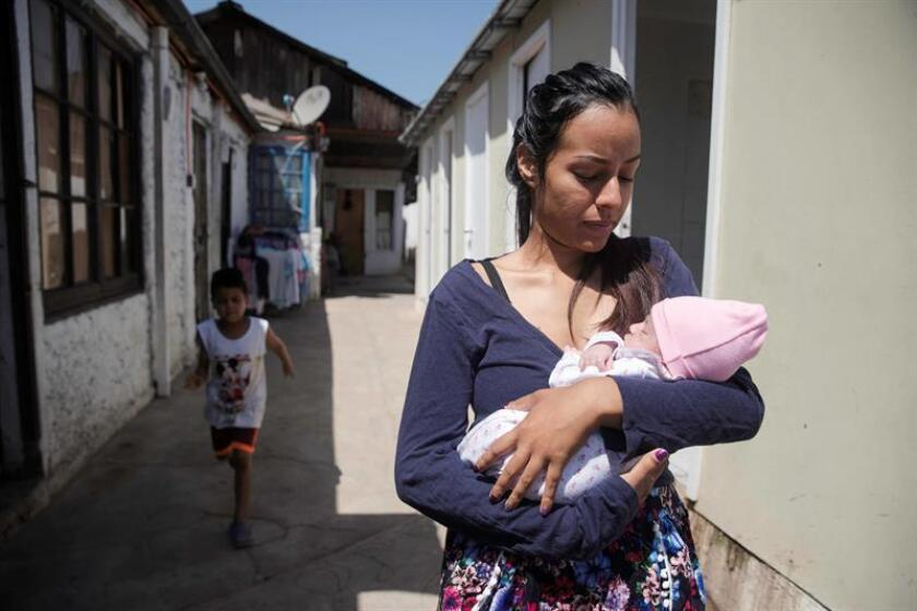 Venezuelan migrant and mother Paulina Lereico walks with her baby on Feb. 18, 2019, at the shelter in Santiago where evangelical Pastor Bernabe Bazan offers lodging, food and hope to more than 80 Venezuelans at a time, and where some 400 migrants have stayed after fleeing the crisis in that country. EFE-EPA/Alberto Valdes
