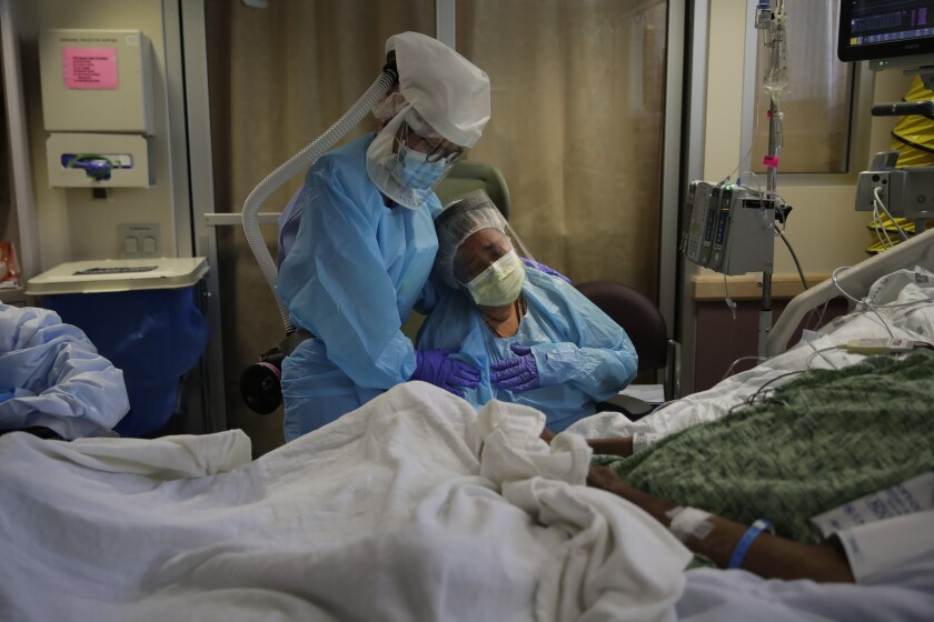 A nurse comforts a grieving woman in St. Jude Medical Center's COVID-19 unit in Fullerton.