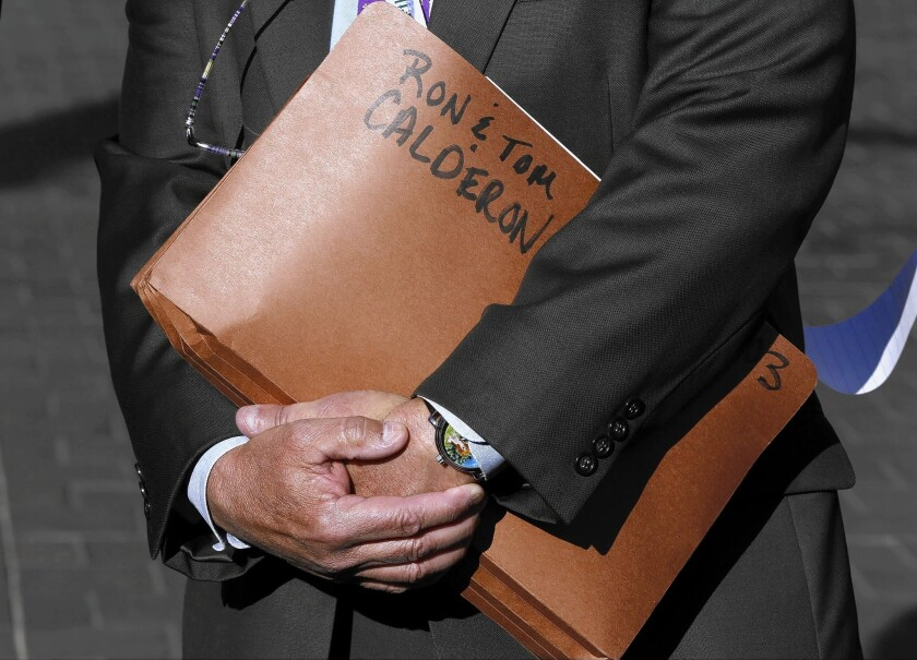 State Department of Justice Public Affairs Officer Thom Mrozek holds a folder tagged with the names of California state Sen. Ronald Calderon and his brother Tom Calderon at a news conference Feb. 24.