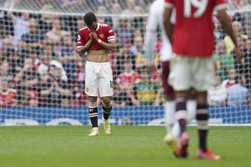 Manchester United's Bruno Fernandes reacts after missing a penalty shot during the English Premier League soccer match between Manchester United and Aston Villa at the Old Trafford stadium in Manchester, England, Saturday, Sept 25, 2021. (AP Photo/Jon Super)