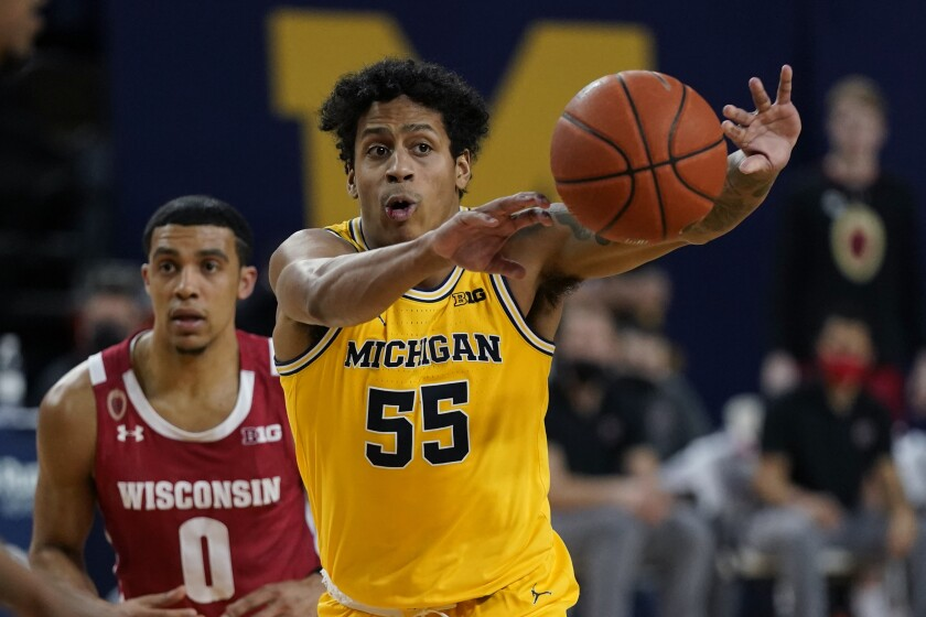 Michigan guard Eli Brooks (55) passes the ball, next to Wisconsin guard D'Mitrik Trice (0) during the second half of an NCAA college basketball game Tuesday, Jan. 12, 2021, in Ann Arbor, Mich. (AP Photo/Carlos Osorio)