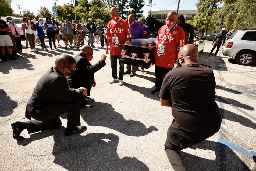Pastors Dewayne Winrow and James Thomas kneel as pallbearers carry an empty casket in memory of George Floyd in Los Angeles.