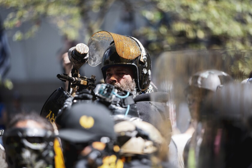 """Alan Swinney points a paintball gun at a group of counterprotesters, Saturday, Aug. 22, 2020, in Portland, Ore. Far-right organizers with the stated goal of """"saying no to Marxism"""" clashed with other demonstrators at the Justice Center in Portland, drawing multiple counterprotests from left-wing, anti-fascist groups and Black Lives Matter groups. The top U.S. prosecutor in Oregon on Wednesday, Sept. 30, 2020, rejected a request from Portland's mayor to end the federal deputation of dozens of police officers as part of the response to ongoing protests, saying it was the only way to end """"lawlessness."""" (Brooke Herbert/The Oregonian via AP)"""