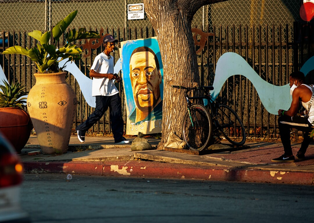 A man walks by a painting of George Floyd in Leimert Park..