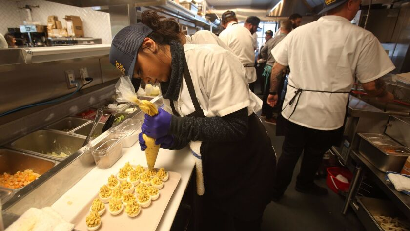 Joanne Hollen, a kitchen staffer at the soon-to-open Crack Shack restaurant in Encinitas, makes a tray of deviled eggs.