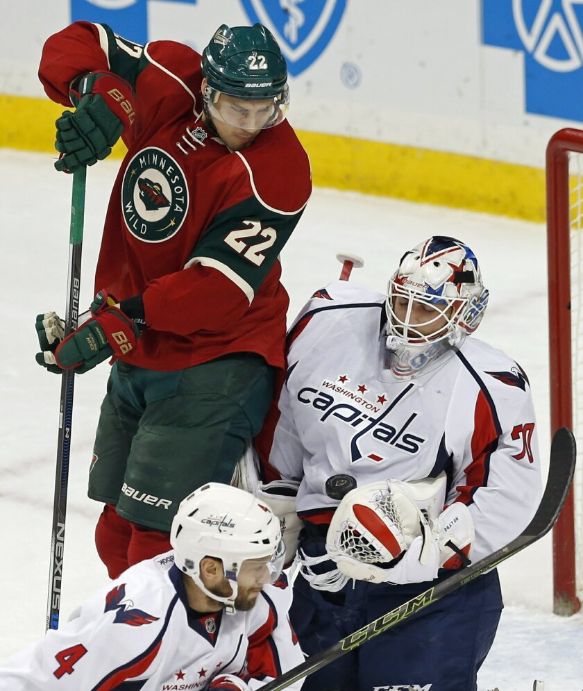 Minnesota Wild's Nino Niederreiter, left, of Switzerland, looks on to see Washington Capitals goalie Braden Holtby stop a shot in the first period of an NHL hockey game, Thursday, Feb. 11, 2016, in St. Paul, Minn. (AP Photo/Jim Mone)