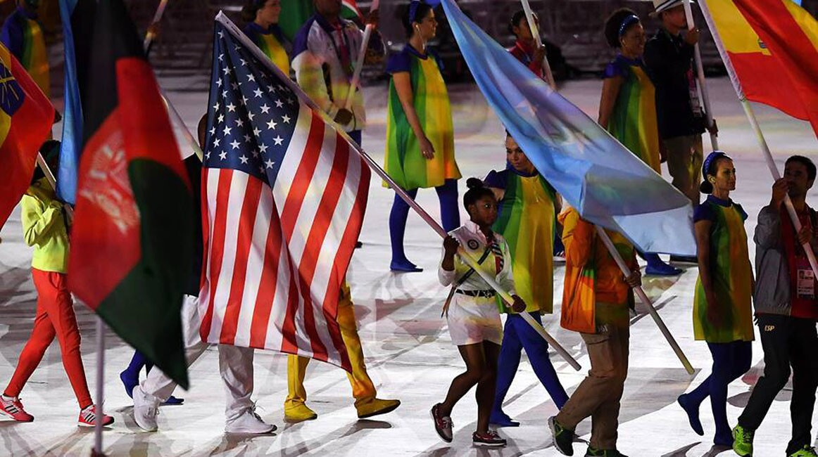 """Flag bearer Simone Biles of United States walks during the """"Heroes of the Games"""" segment during the Closing Ceremony on Day 16 of the Rio 2016 Olympic Games at Maracana Stadium on August 21, 2016 in Rio de Janeiro, Brazil."""