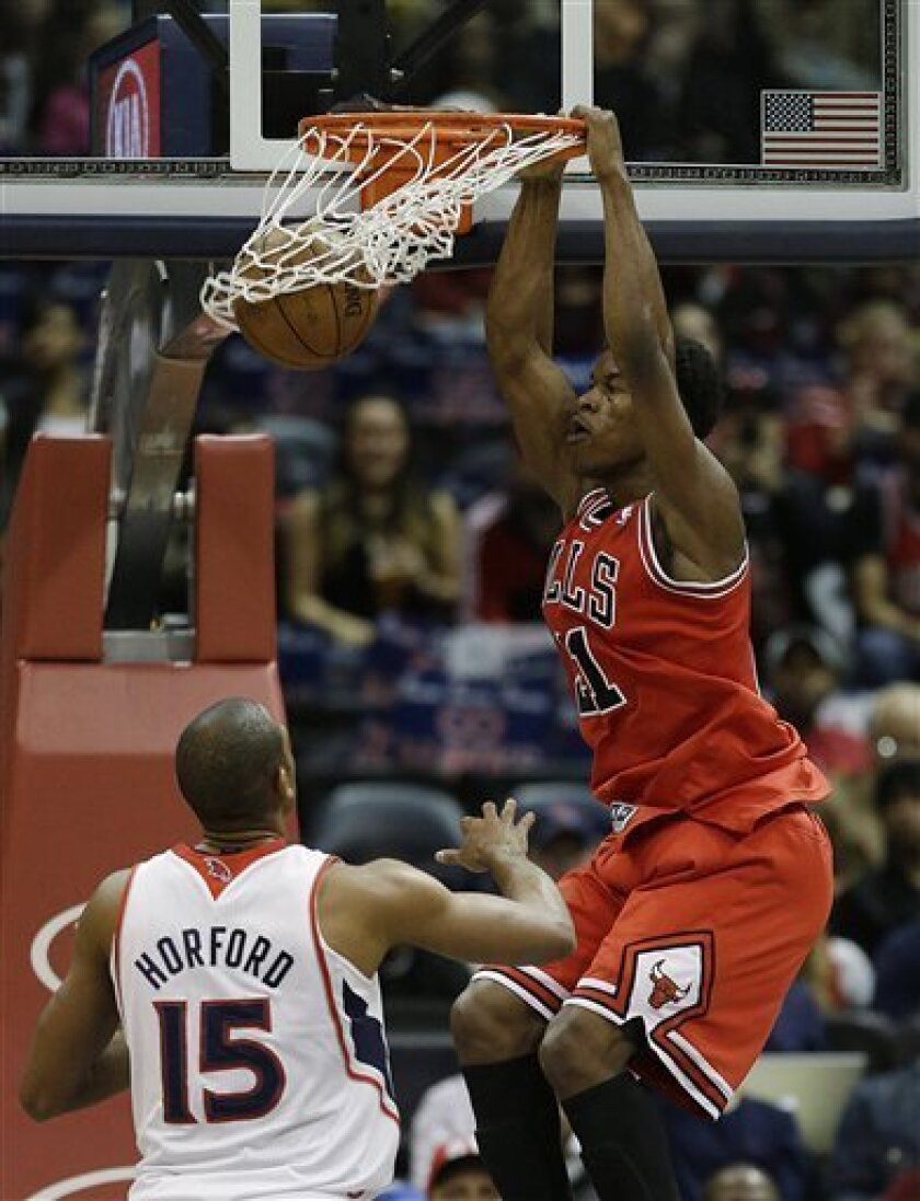 Chicago Bulls forward Jimmy Butler (21) scores against Atlanta Hawks center Al Horford (15) in the first half of an NBA basketball game Saturday, Feb. 2, 2013 in Atlanta. (AP Photo/John Bazemore)