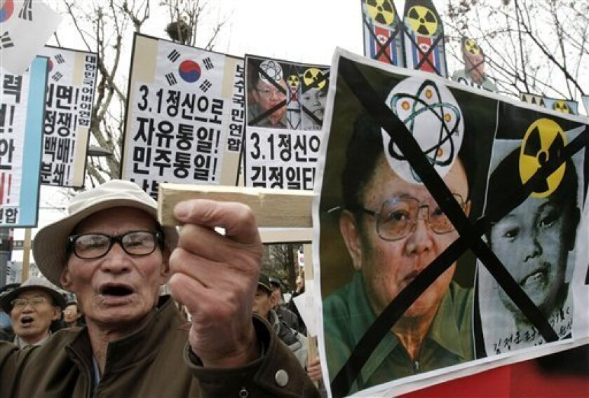 """A South Korean protster with a defaced photo of North Korean leader Kim Jong Il and what protesters say is Kim's youngest son Kim Jong Un, right, shouts slogans during a rally to mark the March First Independence Movement Day, the anniversary of the 1919 uprising against Japanese colonial rule, in Seoul, South Korea, Monday, March 1, 2010. South Korea's president Lee Myung-bak said Monday that he wants to achieve """"genuine"""" reconciliation with North Korea through dialogue and renewed his offer of a package of incentives for the North's nuclear disarmament. (AP Photo/Ahn Young-joon)"""