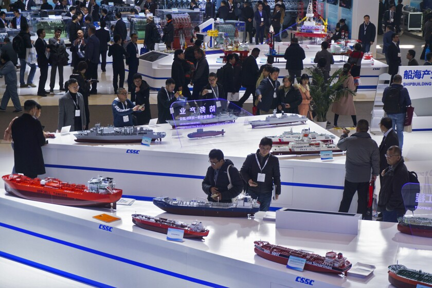 Visitors look at the ship models exhibited by the China State Shipbuilding Corp. (CSSC) during the Marintec China exhibition in Shanghai earlier this month.
