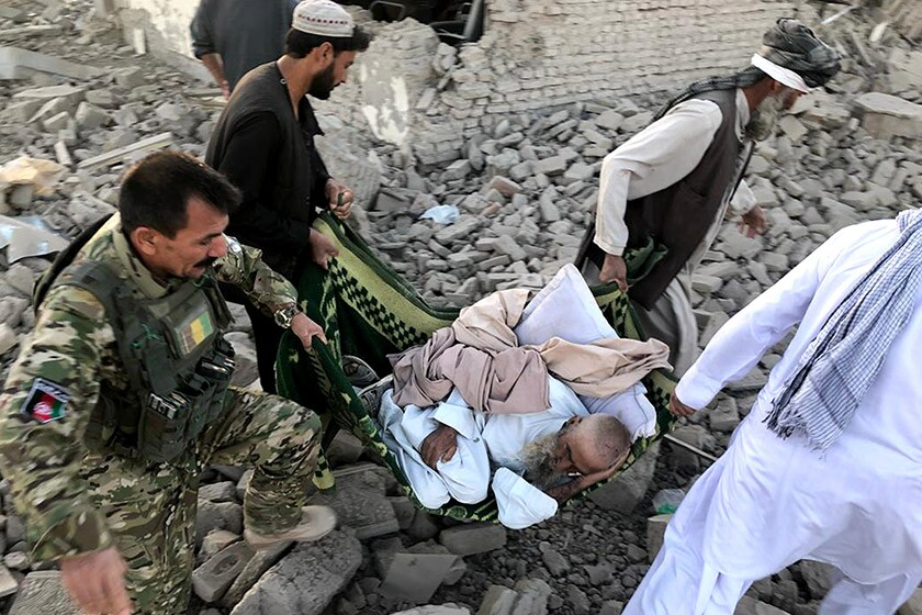An injured man is carried from the scene of a suicide bombing Sept. 19 in Zabul province, Afghanistan.
