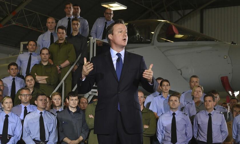 """El primer ministro de Bretaña, David Cameron, se dirige a aviadores de la fuerza aérea Royal durante una visita a RAF Coningsby, Inglaterra, el lunes 13 de julio de 2015. El ejército británico deberá invertir más en drones y tropas élite para contrarrestar la amenaza del grupo Estado Islámico, dijo el lunes el primer ministro David Cameron, y agregó que el terrorismo es una """"amenaza creciente"""" a la que se enfrenta el Reino Unido. (Joe Giddens/PA vía AP)"""