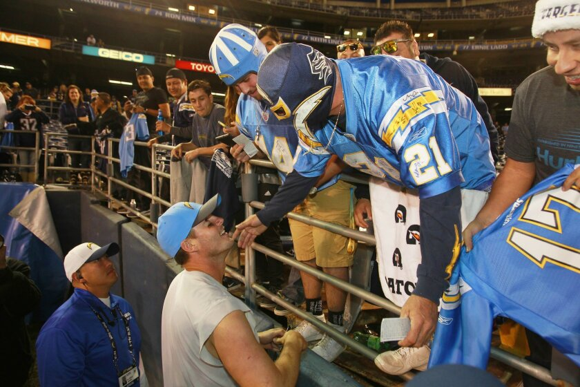 Chargers quarterback Philip Rivers hugs fan Renan Pozo after a 30-14 win over Miami.