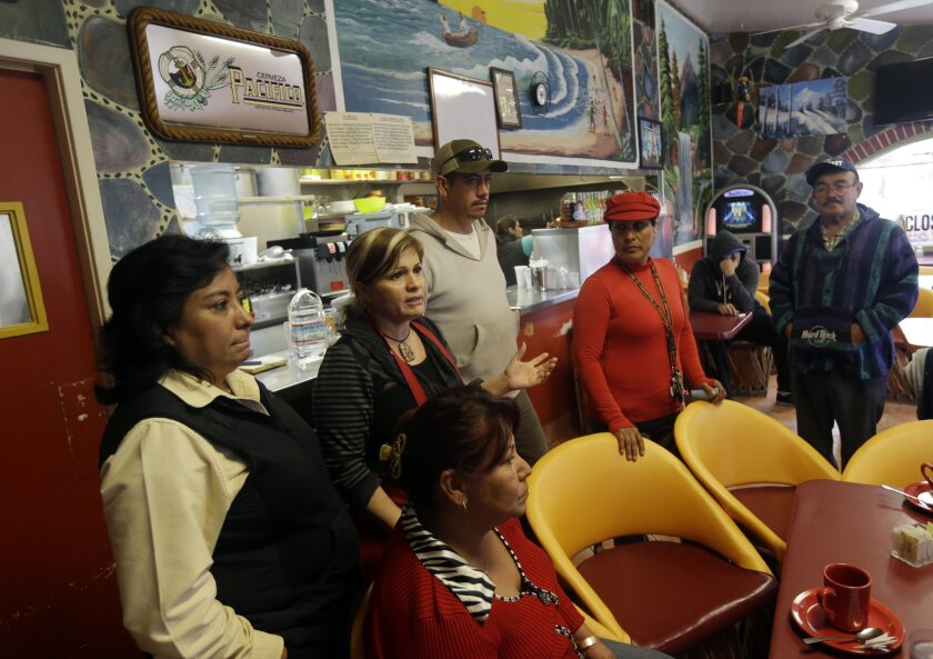 King City residents gather at Veronica Villa's, center with red apron, restaurant to discuss a police car theft ring on Wednesday, Feb. 26, 2014, in King City, Calif. The district attorney charged four police officers and a civilian in a scheme to steal cars from poor Latinos by having their cars impounded at a local tow yard. When the motorists were unable to pay their fees, the tow yard operator sold the cars or gave them for free to police officers. (AP Photo/Marcio Jose Sanchez)